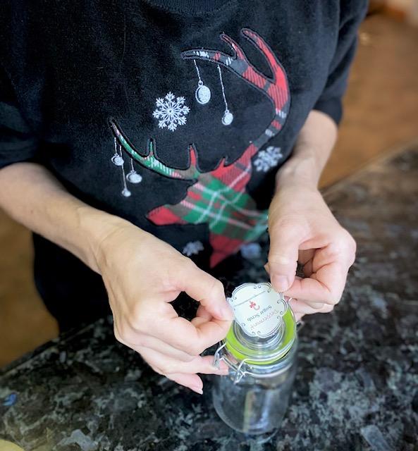 woman placing peppermint sugar scrub label on jar