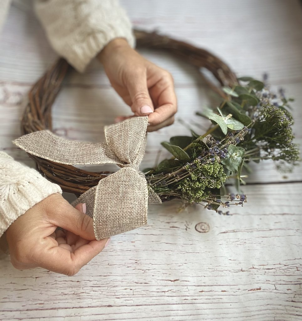 tying a bow on a natural spring wreath