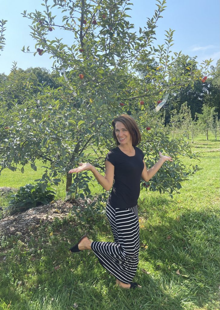 mama in front of apple tree in backyard