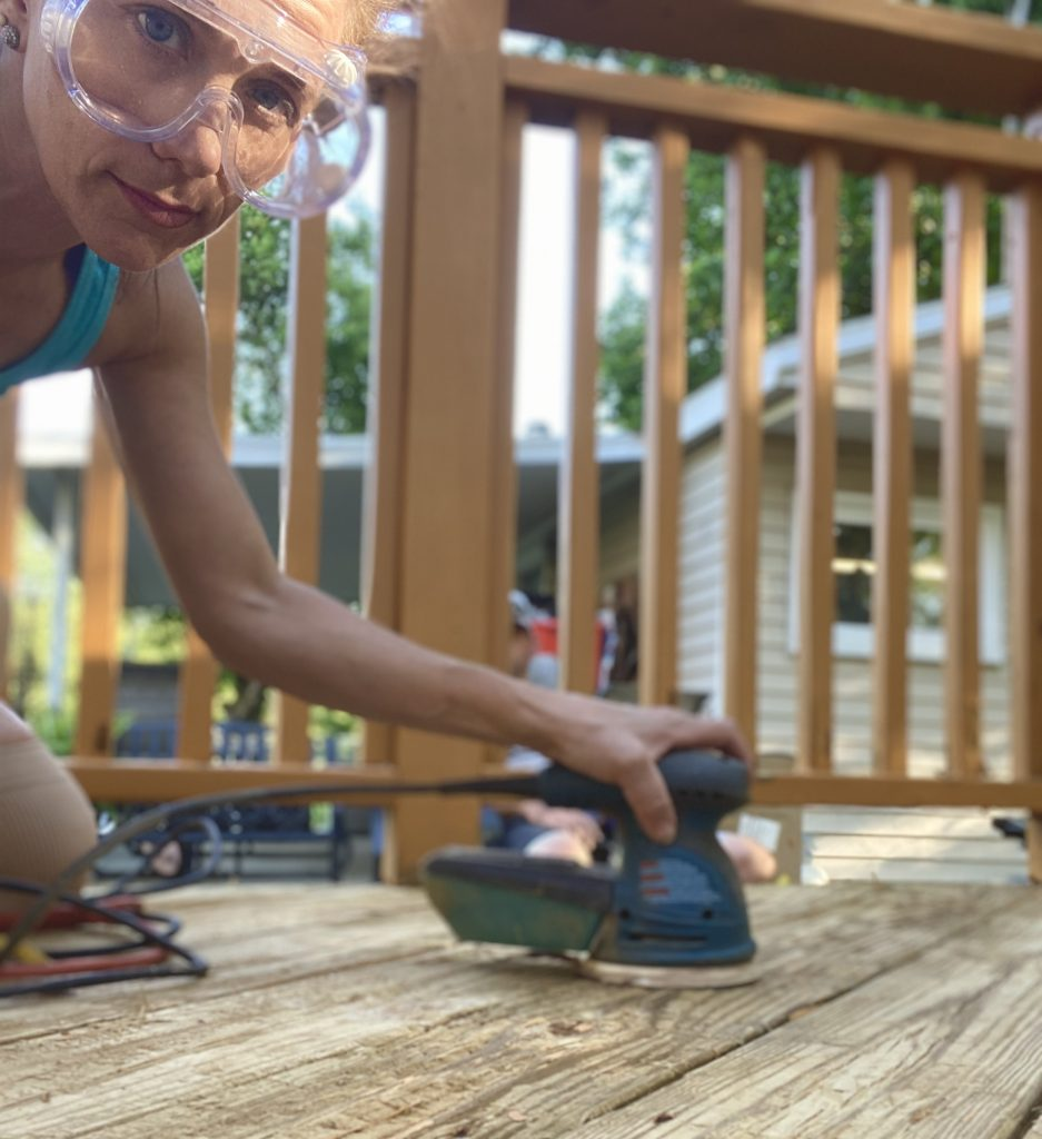 woman sanding a beck deck with a electric sander