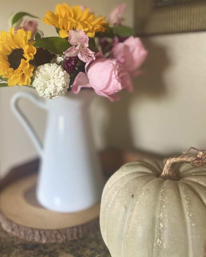 fall flowers in a white pitcher with a green pumpkin
